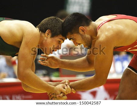 SHERBROOKE, CANADA - August 7: New Brunswick's Geno Poirier wrestles against Ontario's Raj Gill at the Canada Games August 7, 2013 in Sherbrooke, Canada. - stock photo