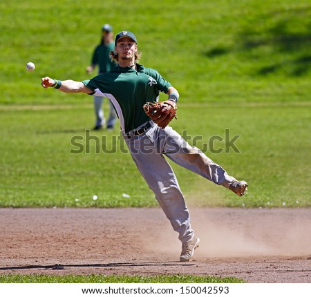 SHERBROOKE, CANADA - August 6: Prince Edward Island shortstop Jay Oram throws to first base in men's baseball at the Canada Games August 6, 2013 in Sherbrooke, Canada. - stock photo