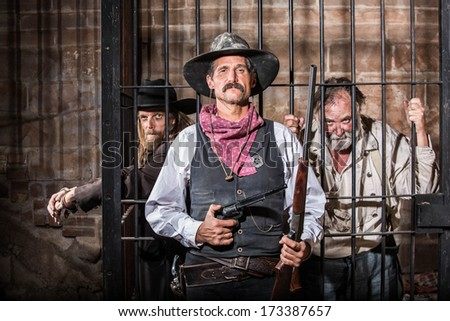 Sheriff Stands Stern in Front of a Jail Cell - stock photo