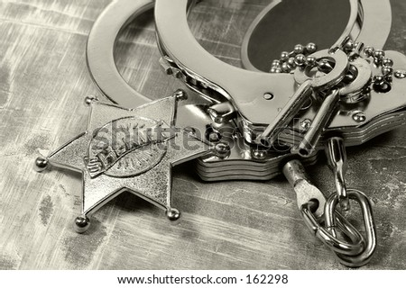Sheriffs Badge and Handcuffs.  See Portfolio For Similar Concepts - stock photo