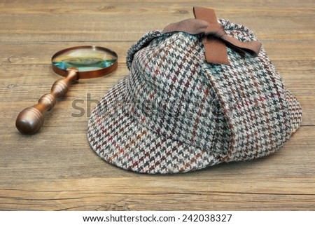 Sherlock Holmes Hat or  Deerstalker Hat and Retro Magnifying Glass on Wooden Table - stock photo
