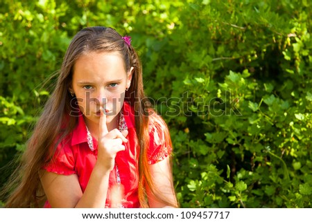 Shh. secret! Beautiful young girl with her finger over her mouth, hushing. - stock photo
