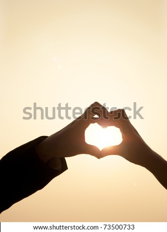 Shiloutte of two hands join to form a heart shape with sun beam inside the heart - stock photo
