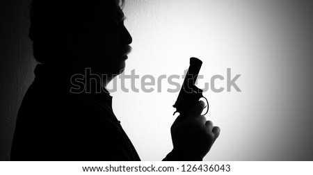 shiluette of man with a revolver, black white - stock photo