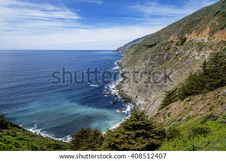 Shimmering aquamarine sea, blue skies, white clouds & gentle waves splashing along the rugged Big Sur coastline, viewed from jagged cliffs of Ragged Point by Highway 1 on the California Central Coast - stock photo