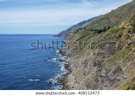 Shimmering aquamarine sea, blue skies, white clouds & gentle waves splashing along the rugged Big Sur coastline, viewed from jagged cliffs of Ragged Point by Highway 1 on the California Central. - stock photo