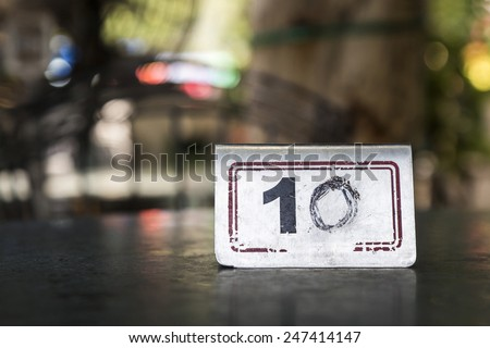 shine metal sign number ten on table in blur background - stock photo