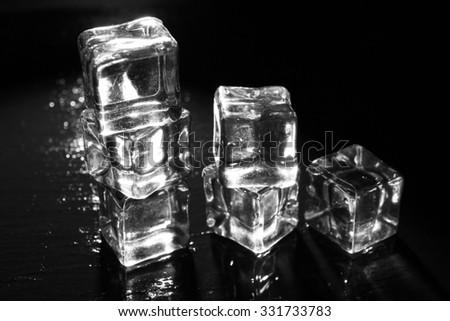 Shining ice cubes on dark liquid background - stock photo