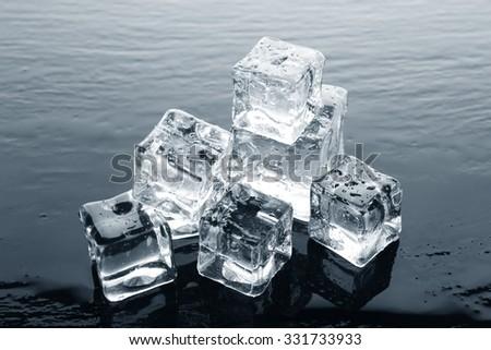 Shining ice cubes on liquid background - stock photo