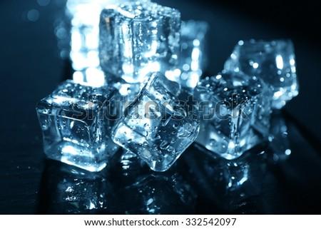 Shining ice cubes under blue light on liquid background - stock photo
