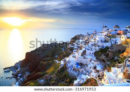 Shining light illuminates traditional white buildings on the Oia village and the sea, Santorini island, Greece - stock photo