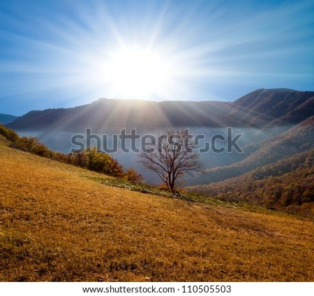 shining sun over a mountain valley - stock photo