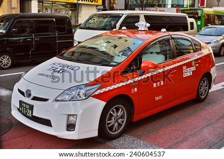 SHINJUKU, TOKYO - DECEMBER 27, 2014: Toyota Prius hybrid vehicle taxi, painted with orange and white. Photographed in the commercial district of Shinjuku, Tokyo. - stock photo