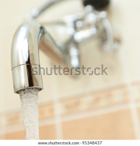 Shinny faucet attached to a wall - stock photo