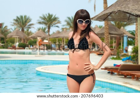 Shiny beautiful girl. Portrait of beautiful young women in bikini smiling on camera with a swimming pool on the background - stock photo