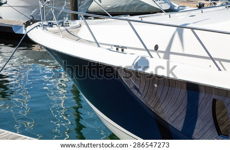 Shiny blue hull on a white yacht in harbor - stock photo