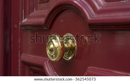 Shiny brass metal doorknob on maroon red wooden entrance door, secure entry to house - stock photo