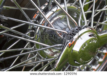 Shiny bright chrome wire wheels and spinners off a classic British sports car. - stock photo
