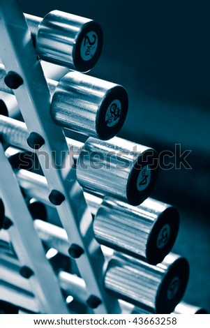 Shiny chrome dumbbells in a row in gym - stock photo