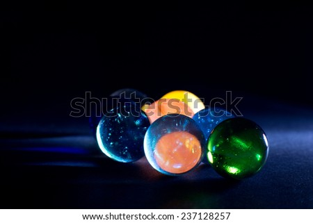 Shiny Colorful Translucent Glass Balls Against Black Background - stock photo
