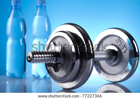 shiny dumbell and bottles of water - stock photo