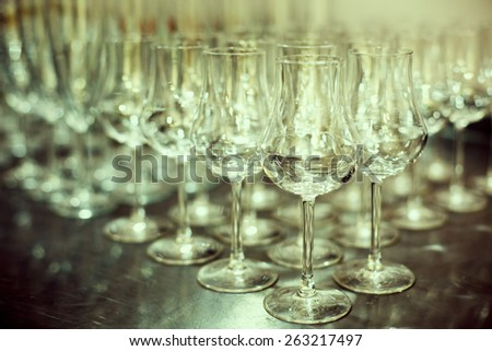 Shiny High Glasses Ready for Drinks. Restaurant, Catering Concept. Selective focus, shallow DOF. Image toned in cyan colors. - stock photo