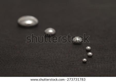 Shiny Mercury drops on a black background - stock photo