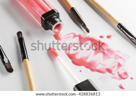Shiny microelents of the lipstick poured out of its tube with an applicator near it. Scattered brushes for lip contouring. Creative chaos during the process of applying make-up. - stock photo