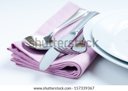Shiny new cutlery, silverware and a napkin close-up on white background - stock photo