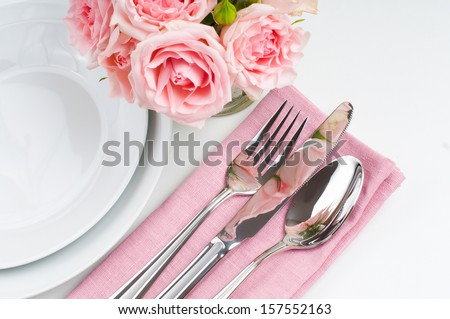 Shiny new cutlery, silverware and a napkin with flowers, close-up on white background - stock photo