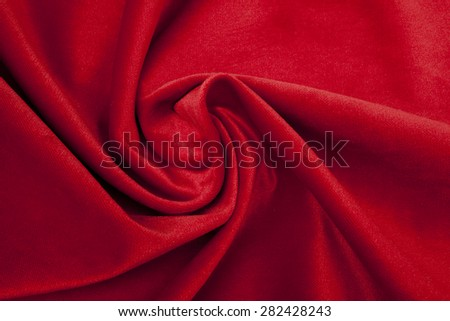 shiny red fabric - arranged in a whirl - stock photo