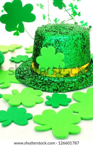 Shiny St Patrick's Day hat with shamrocks over white - stock photo