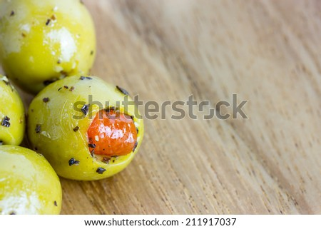 Shiny stuffed pimento olives with crushed black pepper on wooden chopping board. Great as a background. - stock photo