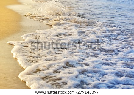 Shiny tropic sea wave on golden beach sand in sunset light - stock photo