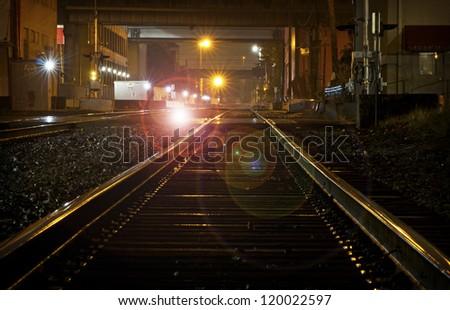 Shiny wet train tracks reflecting lights at night - stock photo