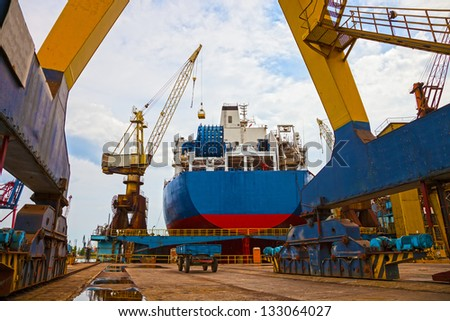 Ship and monumental crane in the shipyard. - stock photo