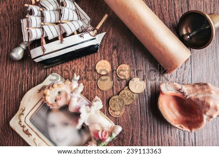 ship frigate parquet scroll coin coinage bell shell sea pirate frame for pictures frame photography memories wooden brown background - stock photo