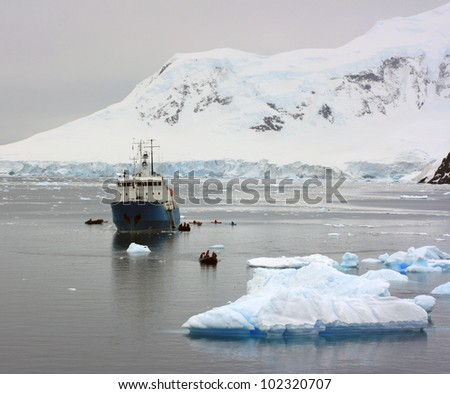 Ship in Antarctic waters beetween snow - stock photo