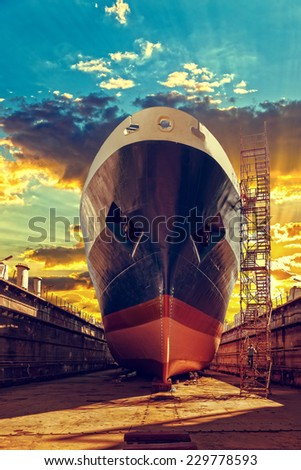 Ship in dry dock at sunrise - shipyard in Gdansk, Poland.  - stock photo