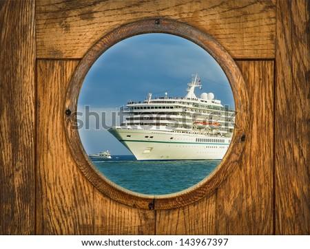 Ship porthole window with seascape and cruise ship. Old porthole on wood background - vintage decoration of sea travel. - stock photo