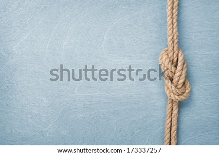 Ship rope knot on blue wooden texture background - stock photo