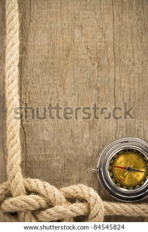 ship ropes and compass on wooden background texture - stock photo