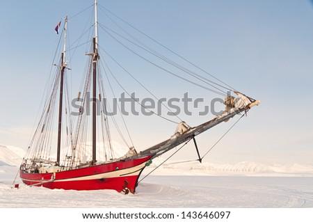 Ship run aground in the sea frozen in the island of svalvard in the Norwegian Arctic - stock photo