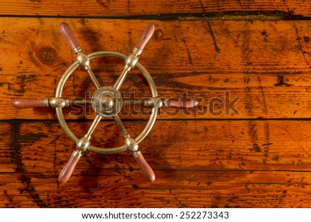 Ship's Wheel on Textured Wood - Brass ship's wheel set against a highly textured wood background.  Vibrant textures and lighting with copy space on right. - stock photo