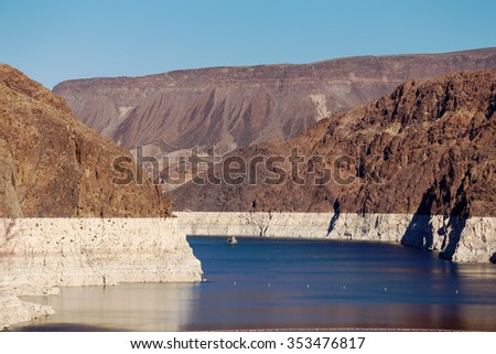 Ship sails on Lake Mead at Hoover Dam. White low water level strip on red cliffs of Lake Mead entering Hoover Dam. - stock photo