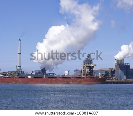 ship unloading in front of a large steel factory in IJmuiden, Netherlands - stock photo