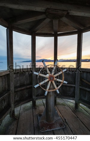 Ship wheel on a wooden quay overlooking an ocean during a beautiful colorful sunset. Taken in Jericho Beach, vancouver, British Columbia, Canada. - stock photo