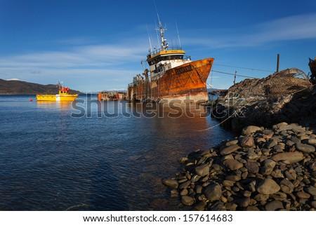 Ship wrec near Ushuaia, Tierra del Fuego. Boats line the harbor  - stock photo