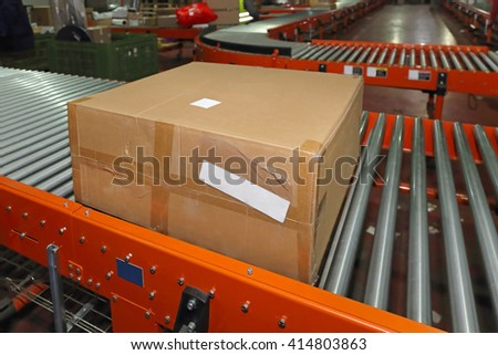 Shipping Box at Conveyor Belt in Distribution Warehouse - stock photo