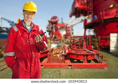 Shipping engineer with a cb-radio on the deck of a large industrial vessel, smiling into the camera on a bright sunny day - stock photo